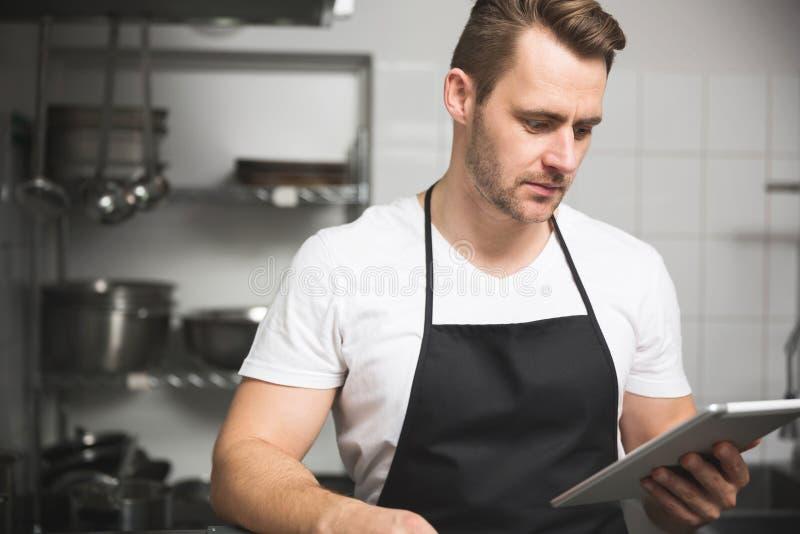 Hübscher Chef, der die Mahlzeit hält Tablette kocht stockfotografie
