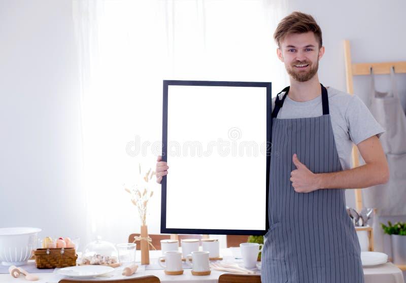 hübscher Chef, der leeres leeres Brettmenüzeichen für Restaurant zeigt stockfotografie