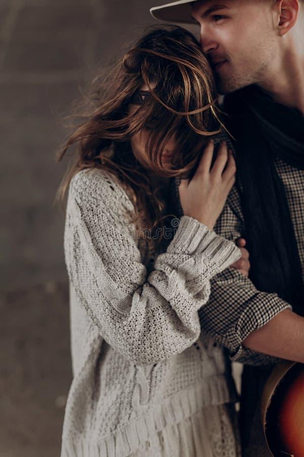 Hübscher Cowboymann mit einer Gitarre schöne indie Frau küssend lizenzfreie stockfotografie
