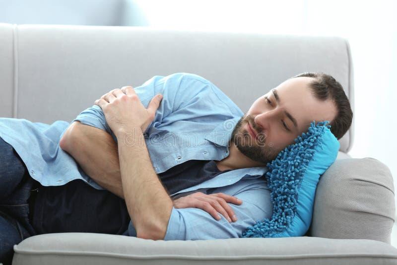 Hübscher deprimierter Mann, der auf Sofa liegt stockfoto