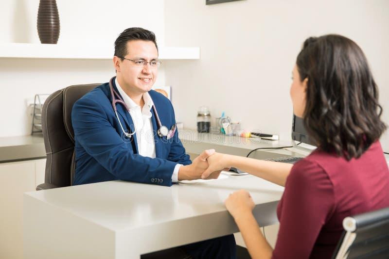 Hübscher Doktor, der einen Patienten grüßt stockfotos