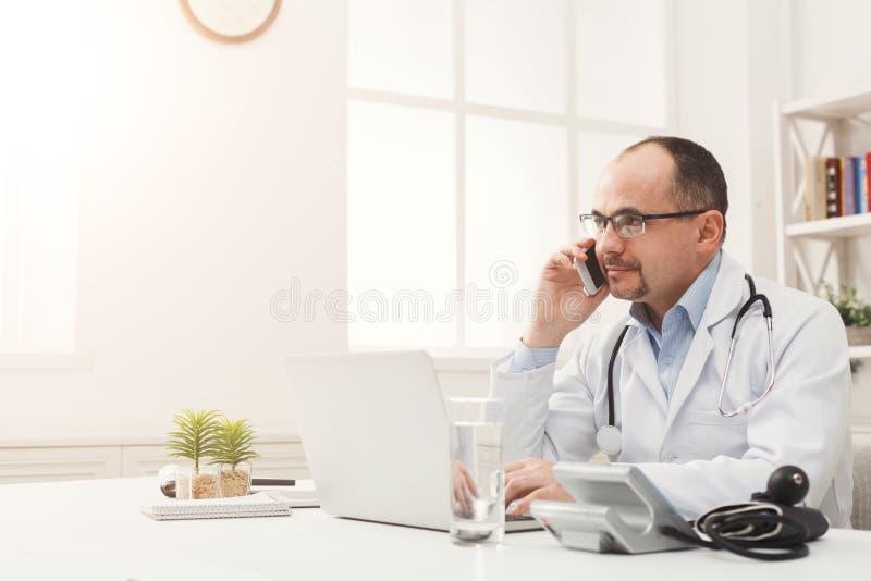 Hübscher Doktor, der am Telefon mit seinem Patienten spricht stockfotos