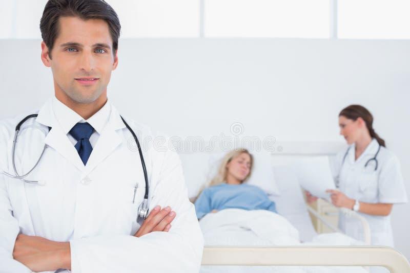 Hübscher Doktor mit den Armen gekreuzt lizenzfreie stockfotos