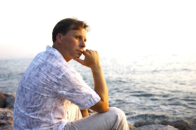 Hübscher durchdachter Mann in dem Meer stockfotos