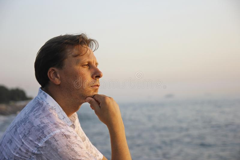 Hübscher durchdachter Mann in dem Meer stockbilder