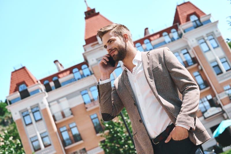 Hübscher eleganter junger Mann in der Stadt, sprechend auf seinem Mobiltelefon beim Lächeln stockfotos