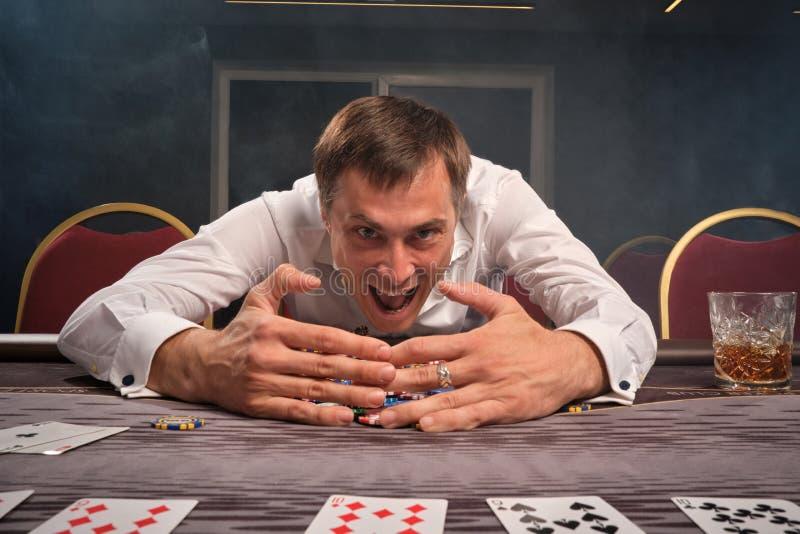 Hübscher emotionaler Mann spielt den Schürhaken, der am Tisch im Kasino sitzt stockbild