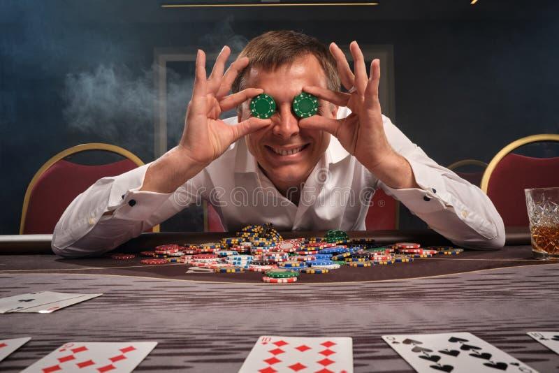 Hübscher emotionaler Mann spielt den Schürhaken, der am Tisch im Kasino sitzt lizenzfreie stockfotografie