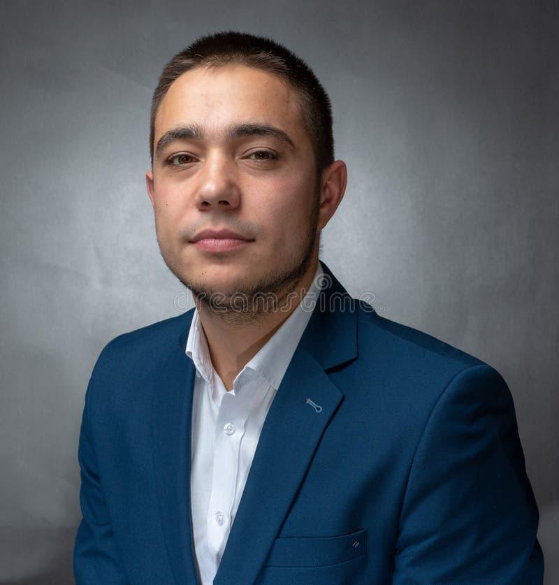Hübscher erfolgreicher Geschäftsmann in der blauen Klage, die Ausdrücke sitzt und zeigt lizenzfreies stockfoto