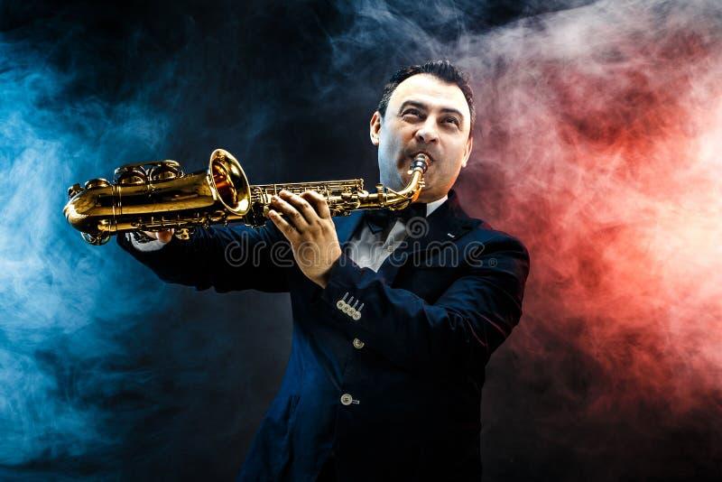Hübscher erwachsener Mann, der Saxophon spielt stockfoto