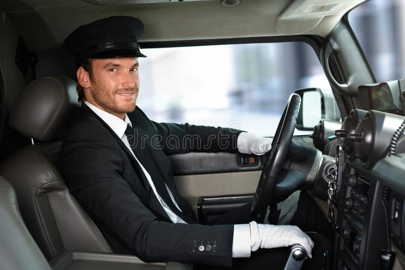 Hübscher Fahrer, der das Limousinenlächeln fährt lizenzfreies stockfoto