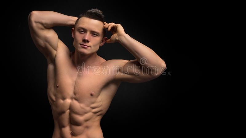 Hübscher Formmann mit muskulösem Körper Nahaufnahme von ` s junger Mann des Sitzes Unterleib gegen dunklen Hintergrund lizenzfreie stockfotografie