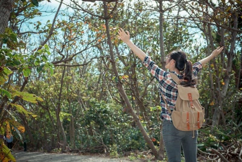 Hübscher Frauenreisender, der im Waldweg steht lizenzfreie stockbilder