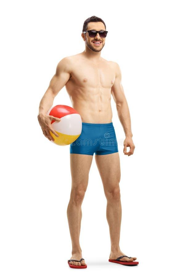 Hübscher geeigneter Mann in den schwimmenden kurzen Hosen, die ein aufblasbares halten lizenzfreie stockbilder