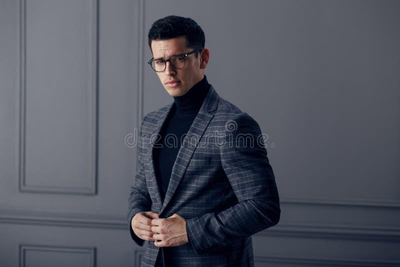 Hübscher, geeigneter Mann im grauen Anzug mit schwarzem Rollkragen, schwarze stilvolle Brillen betrachtet der Kamera überzeugt stockbild