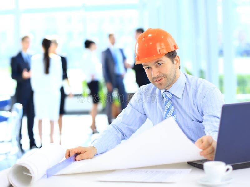 Hübscher Geschäftsbaumann auf dem Arbeitsstandort lizenzfreie stockbilder