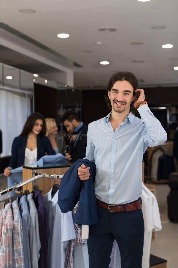 Hübscher Geschäftsmann-Abnutzungs-Gesellschaftsanzug, der Jacke in den Händen im modernen Männerkleidungs-Shop hält lizenzfreie stockfotos