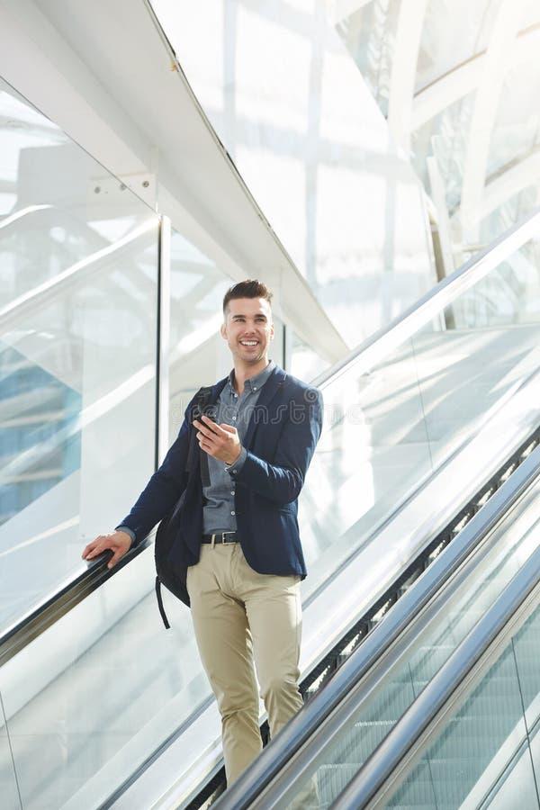 Hübscher Geschäftsmann auf Rolltreppe lächelnd mit intelligentem Telefon lizenzfreie stockfotografie