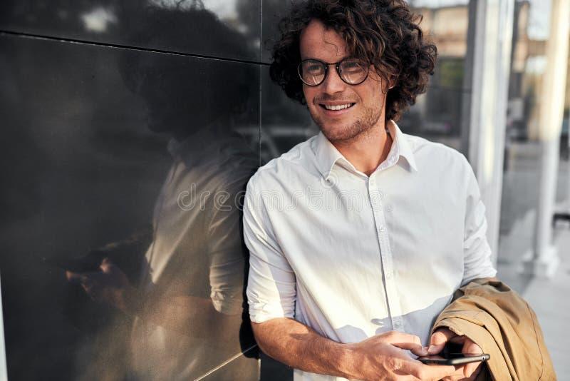 Hübscher Geschäftsmann, der auf einer Wand bei draußen stehen und der Anwendung von Smartphone auf der Straße sich lehnt Glücklic stockbild