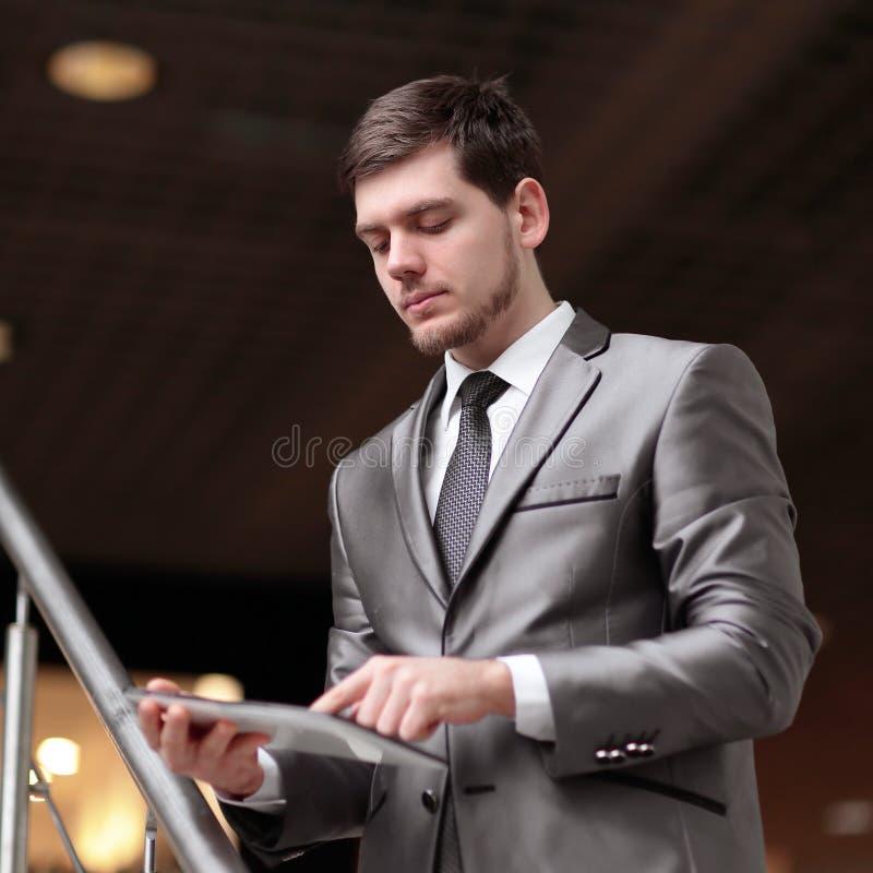 Hübscher Geschäftsmann, der auf Schritten unter Verwendung der Tablette im Bürogebäude steht stockfotografie