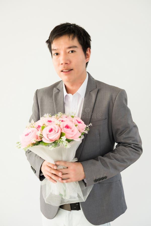 Hübscher Geschäftsmann, der Blumenblumenstrauß hält stockbild