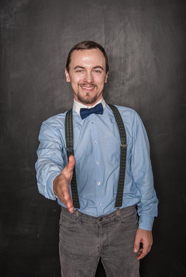 Hübscher Geschäftsmann, der Hand für Händedruck auf Tafel gibt lizenzfreie stockbilder