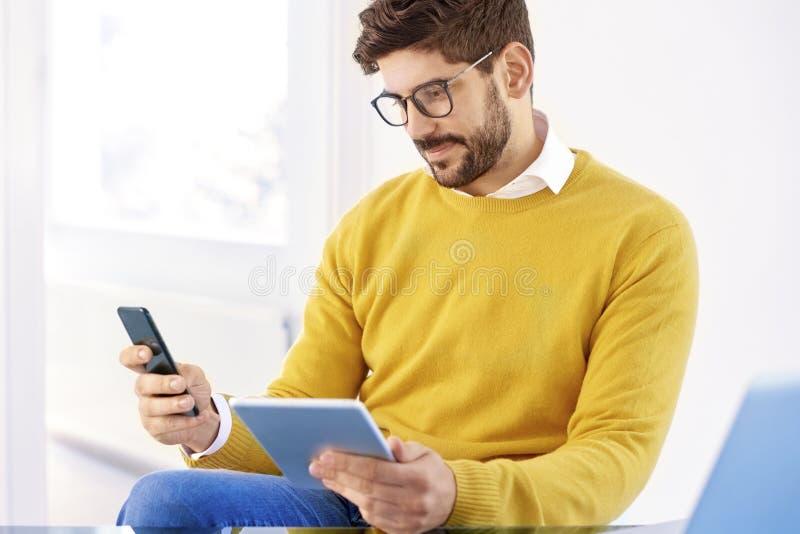 Hübscher Geschäftsmann, der im Büro sitzt und Handy verwendet lizenzfreies stockbild