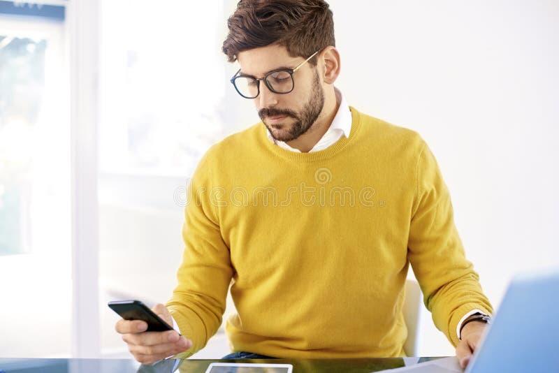 Hübscher Geschäftsmann, der im Büro sitzt und Handy verwendet stockbild