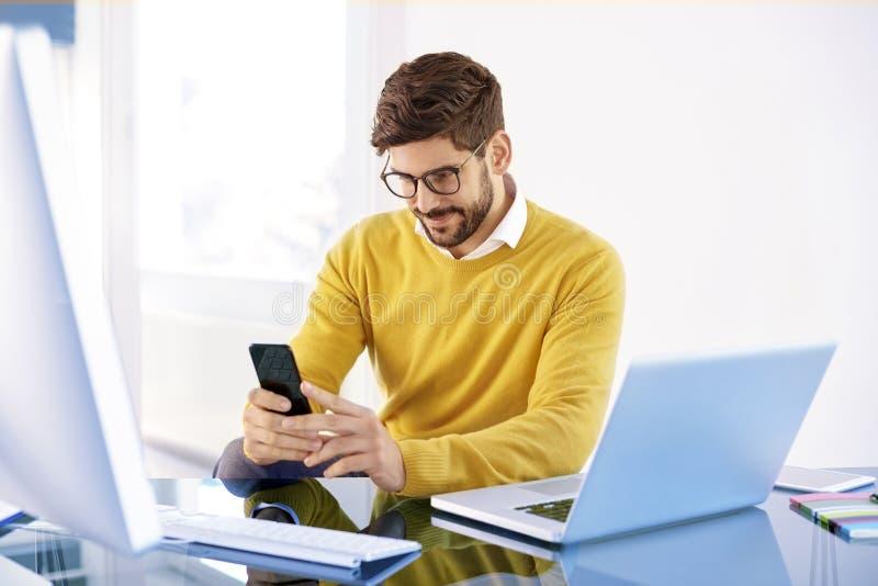 Hübscher Geschäftsmann, der an im Büro und in den Versenden von SMS-Nachrichten sitzt stockbild