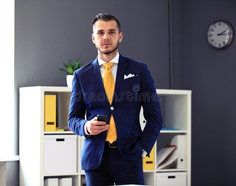 Hübscher Geschäftsmann in der Klage, die Kamera betrachtet lizenzfreies stockfoto