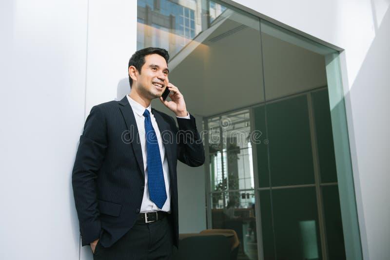 Hübscher Geschäftsmann in der Klage, die am Telefon im Büro spricht stockfotografie