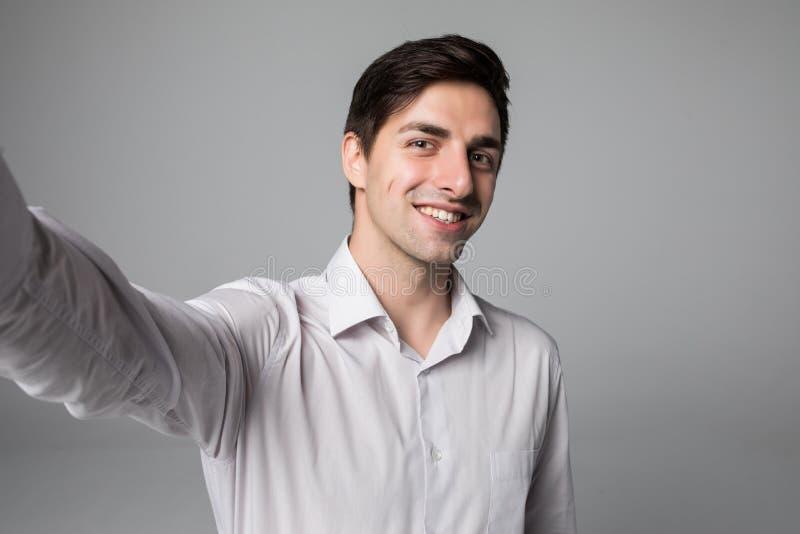 Hübscher Geschäftsmann, der selfie Foto auf Smartphone über grauem Hintergrund macht stockfoto