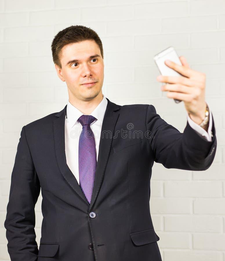 Hübscher Geschäftsmann, der selfie Foto auf Smartphone macht stockbilder