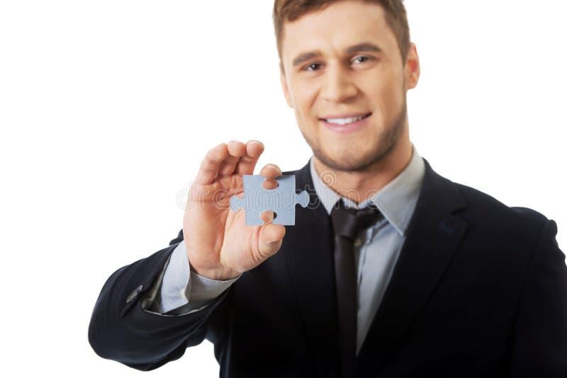 Hübscher Geschäftsmann, der Stück des Puzzlespiels hält lizenzfreie stockfotografie