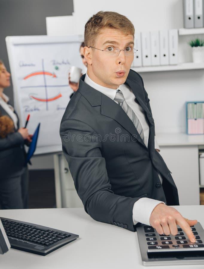 Hübscher Geschäftsmann, der am Taschenrechner berechnet lizenzfreies stockfoto