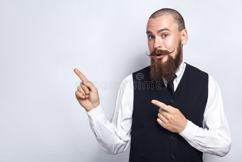 Hübscher Geschäftsmann mit dem Bart- und Lenkstangenschnurrbart, der die Kamera, überrascht betrachtet und Kopienraum mit den Fin stockfotografie