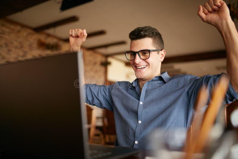 Hübscher Geschäftsmann mit dem Laptop, der seine Arme mit den Fäusten angehoben, Erfolg feiernd hat Glücklicher Freiberuflerhippi stockfotografie