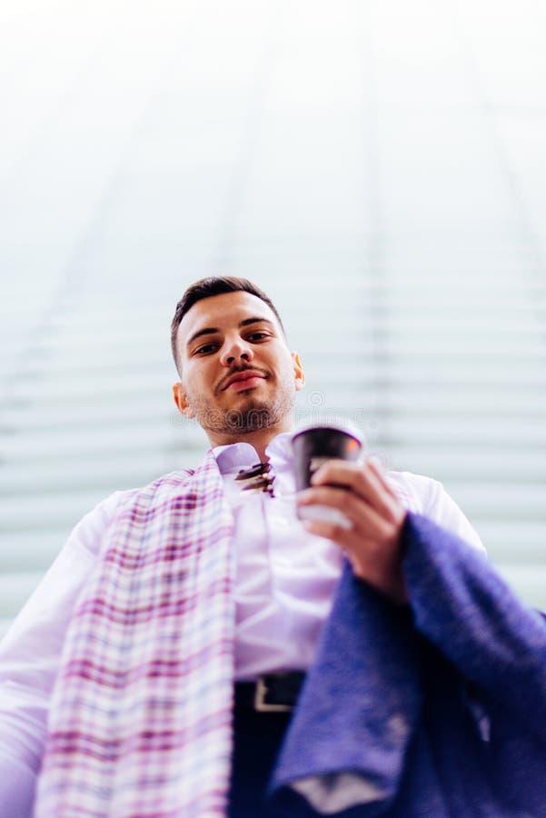 Hübscher Geschäftsmann steht noch, hinter ihm ist ein großes Gebäude, er schaut zufriedengestellt mit einem Kaffee lizenzfreies stockfoto