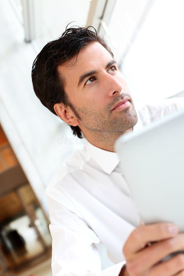 Hübscher Geschäftsmann unter Verwendung der Tablette stockfoto