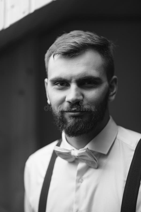 Hübscher glücklicher Bräutigam, der auf stilvolles weißes Hemd vor der Heirat, überzeugter Geschäftsmann sich vorbereitet für das lizenzfreie stockfotos
