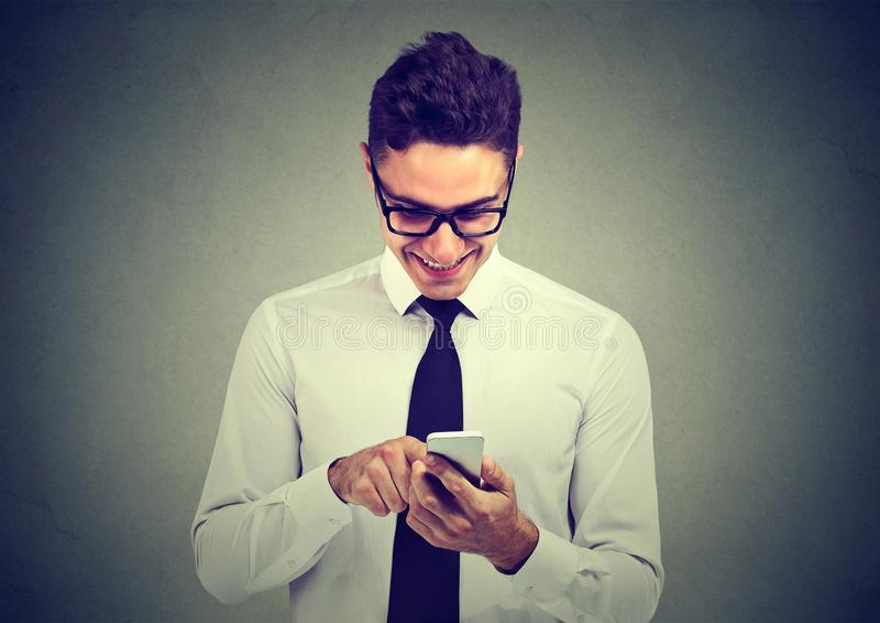 Hübscher glücklicher junger Geschäftsmann, der Handy verwendet lizenzfreie stockbilder