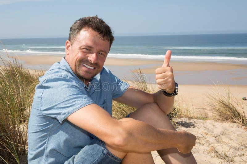 Hübscher glücklicher Mann, der Daumen oben auf dem Strand gibt lizenzfreie stockfotos