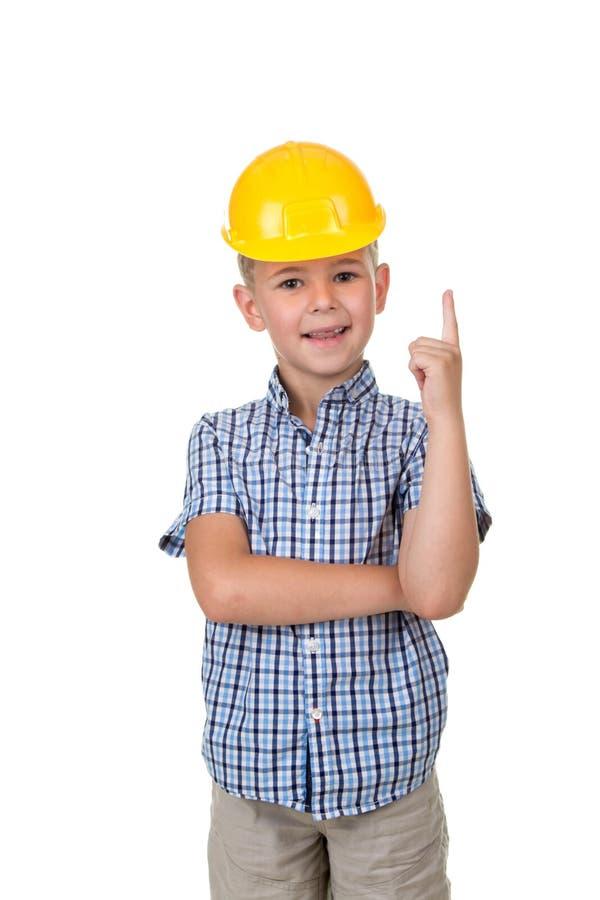 Hübscher glücklicher zukünftiger Erbauer kleidete in Blau checkred grauen Jeans des Hemdes und gelben im Sturzhelm an und gestiku lizenzfreie stockfotografie