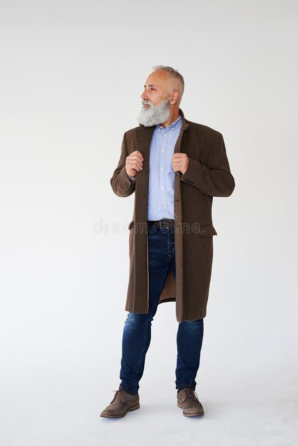 Hübscher grauer bärtiger Mann kleidete im Herbstmantel an stockfotos