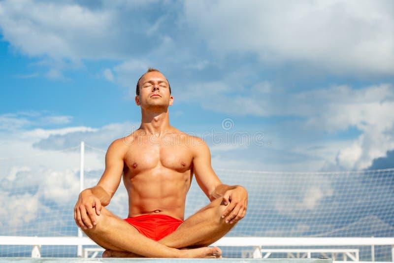 Hübscher hemdloser junger Mann während der Meditation oder des Handelns einer Yoga-Übung im Freien, die gegen den blauen Himmel s stockfoto