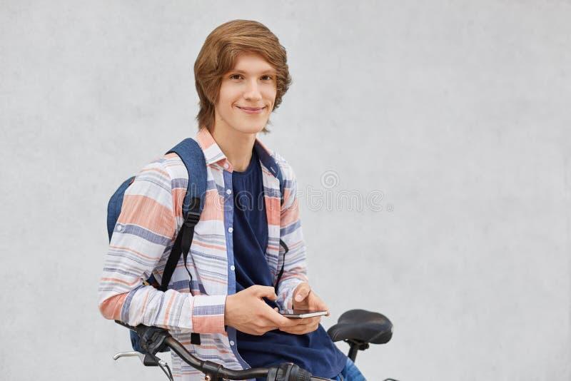 Hübscher Hippie-Kerl mit dem tragenden Hemd und Jeans des modischen Haarschnitts, die den Rucksack sitzt auf dem Fahrrad hält den lizenzfreies stockbild