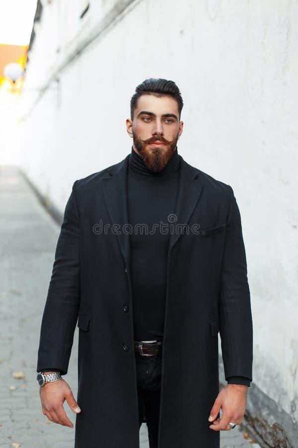Hübscher Hippie-Mann mit einem Bart in einem schwarzen Mantel auf der Straße stockbild