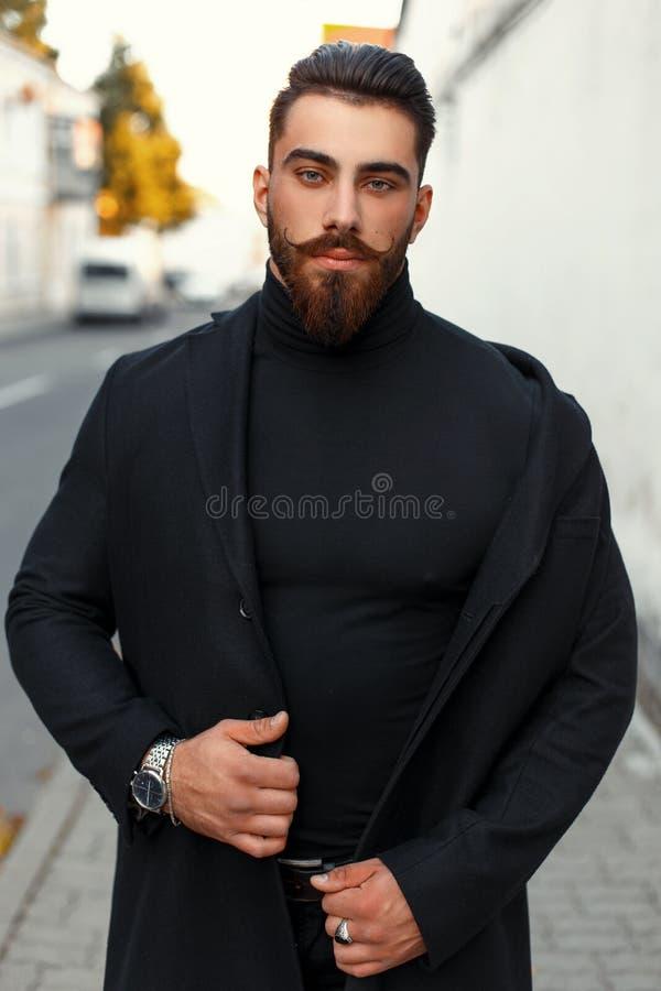 Hübscher Hippie-Mann mit einem Bart in einem schwarzen modischen Mantel lizenzfreies stockbild