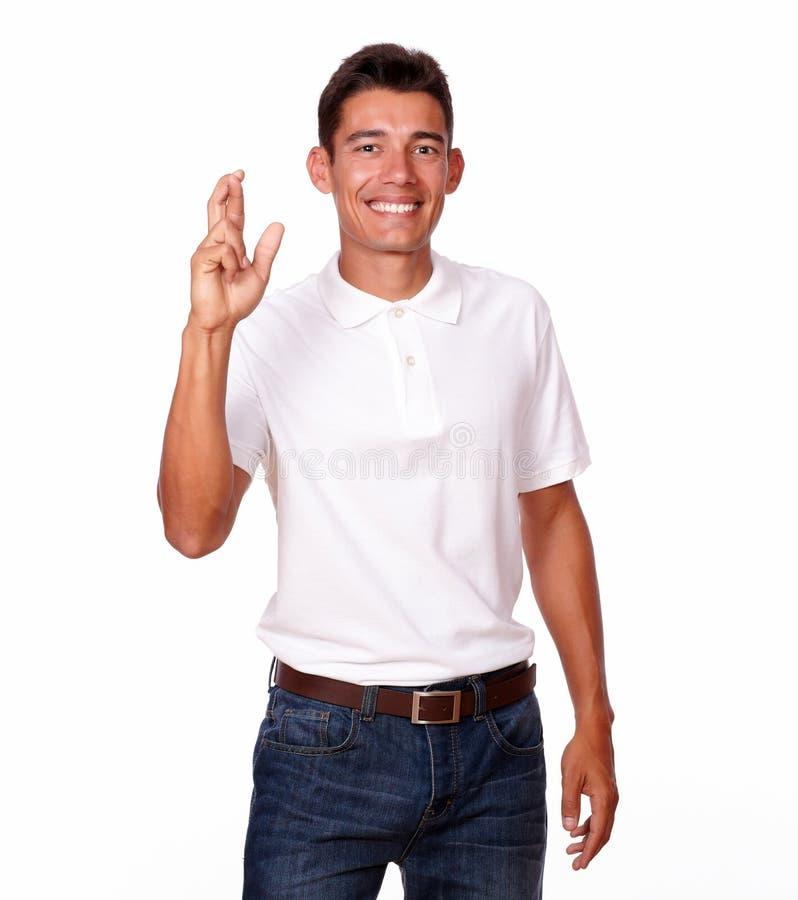 Hübscher hispanischer Mann, der mit einem Fingerzeichen lächelt. stockbilder