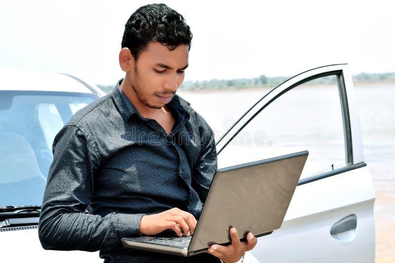 Hübscher indischer Geschäftsmann, der an Laptop mit Auto arbeitet stockfoto